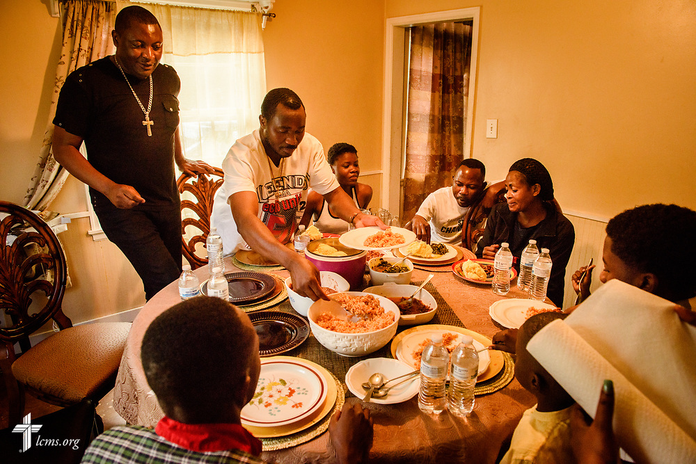 The Rev. Gui Kasongo Kabeo (left), pastor at Eglise Lutherienne Internationale de Sion (International Lutheran Church of Zion) and Gospel Lutheran Church, both in Milwaukee, Wis., oversees dinner at his home on Monday, Aug. 14, 2017 in Milwaukee. Kabeo houses refugees, some seen in this photograph, who do not have a place to go when they arrive in the United States. LCMS Communications/Erik M. Lunsford