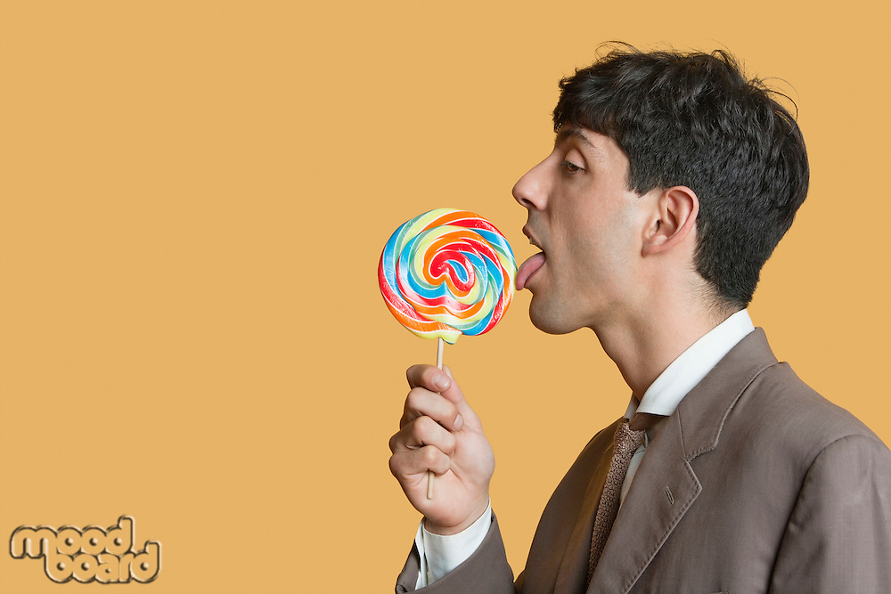 Side view of young businessman licking lollipop over colored background
