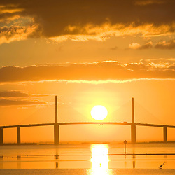 The sun rises behind the Sunshine Skyway Bridge as seen from Fort De Soto Park in Pinellas County, Florida.