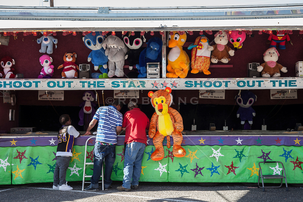 three people standing by a game at a state fair in New Mexico