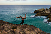 Young woman doing a handstand on coastal rocks, The Gorge, Point Lookout, North Stradbroke Island, Queensland, Australia