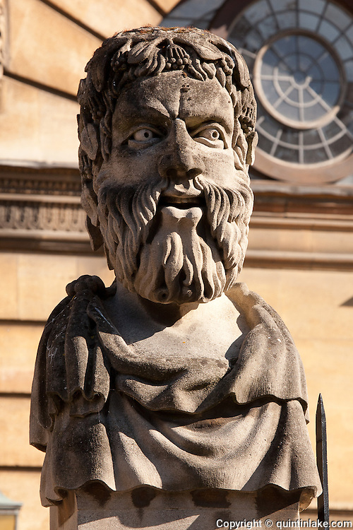 """Emperors Heads, Sheldonian theatre, Broad St, Oxford. The official name for such heads is """"herms""""; the original accounts describe these heads as """"termains""""; and some people call them philosophers. But Max Beerbohm in Zuleika Dobson called them """"Emperors"""", and that is the name that has stuck. Each head shows a different type of beard. The present heads are the third set carved between 1970 and 1972 by Michael Black. The first set lasted 200 years, but by 1868 they were crumbling and new ones were erected; undergraduates, however, daubed these in paint, and the harsh cleaning they received caused them to wear badly, so that they could be described by John Betjeman (in his verse autobiography Summoned by Bells) as """"the mouldering busts round the Sheldonian"""" when he came up in 1925."""