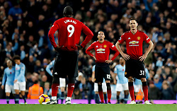 Manchester United's Nemanja Matic (right) an Romelu Lukaku (left) appear dejected after Manchester City's Ilkay Gundogan scores his side's third goal of the game during the Premier League match at the Etihad Stadium, Manchester.