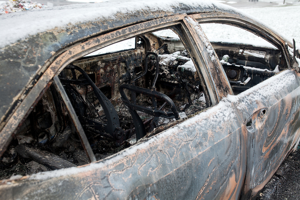 The remains of a burned car on Canfield Dr. The night before, dozens of cars and businesses were torched by arsonists and looters.