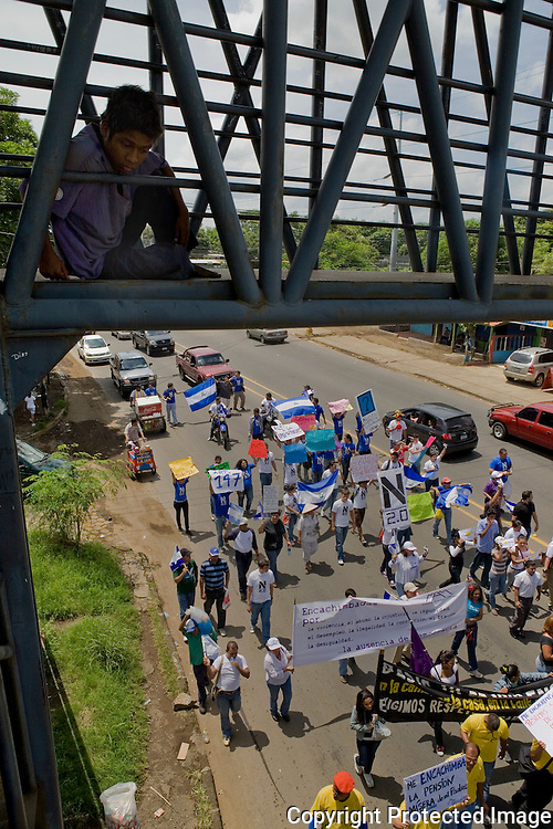 An onlooker watches the Contra Ortega Protest, Nicaragua pass by from a bridge in Managua Nicaragua