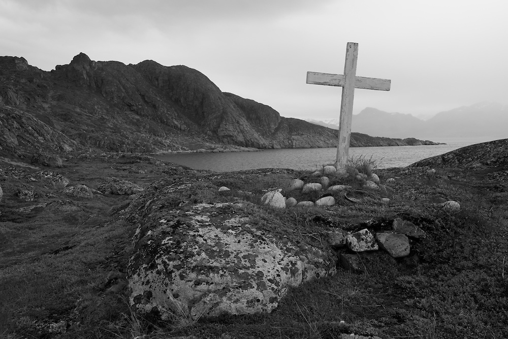 Greenland, Nanortalik, Weathered wooden cross marks memorial on rocky headland near mouth of Tasermiut (Ketils Fjord)