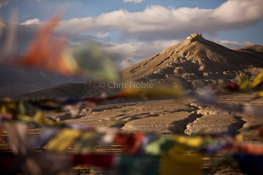 The evening sun illuminates prayer flags on the roof of a Lo Manthang monastery below a view of an ancient fortress on the surrounding hills.