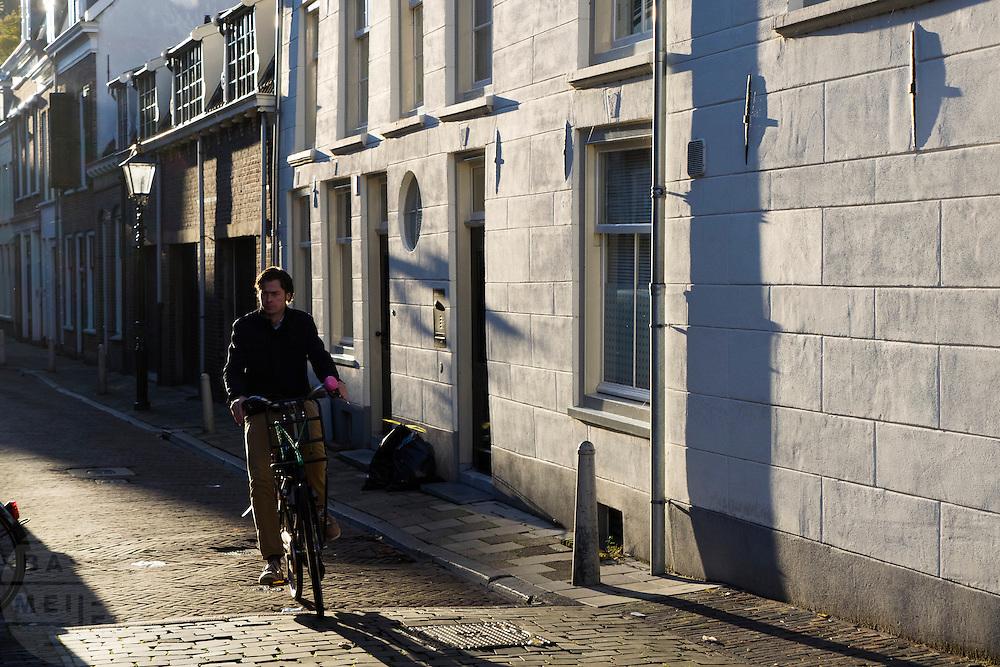 Een man fietst door de Geertestraat in Utrecht.<br /> <br /> A man cycles at the Geertestraat in Utrecht.