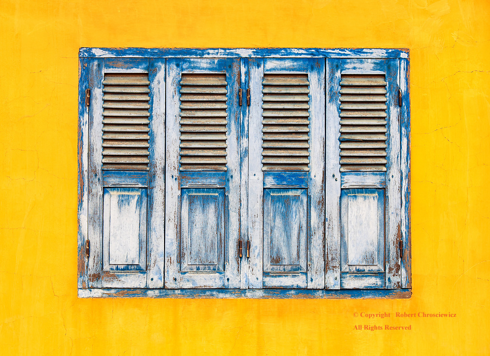 Worn Point of View: A well worn, blue shuttered window set against a bright yellow wall of the Buddhist temple, Wat Tahm Rai Saw, Battambang Cambodia.