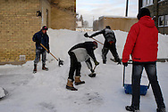 Four men shovel and plow snow from the Worth a Second Look parking lot in Kitchener, Ontario, Canada. The men are doing casual labour for Job Cafe, a program of The Working Centre and the owner of the second hand store.