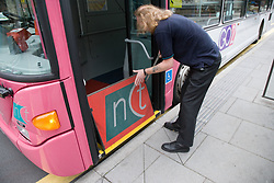 Bus driver lifting up ramp used by wheelchair users,,