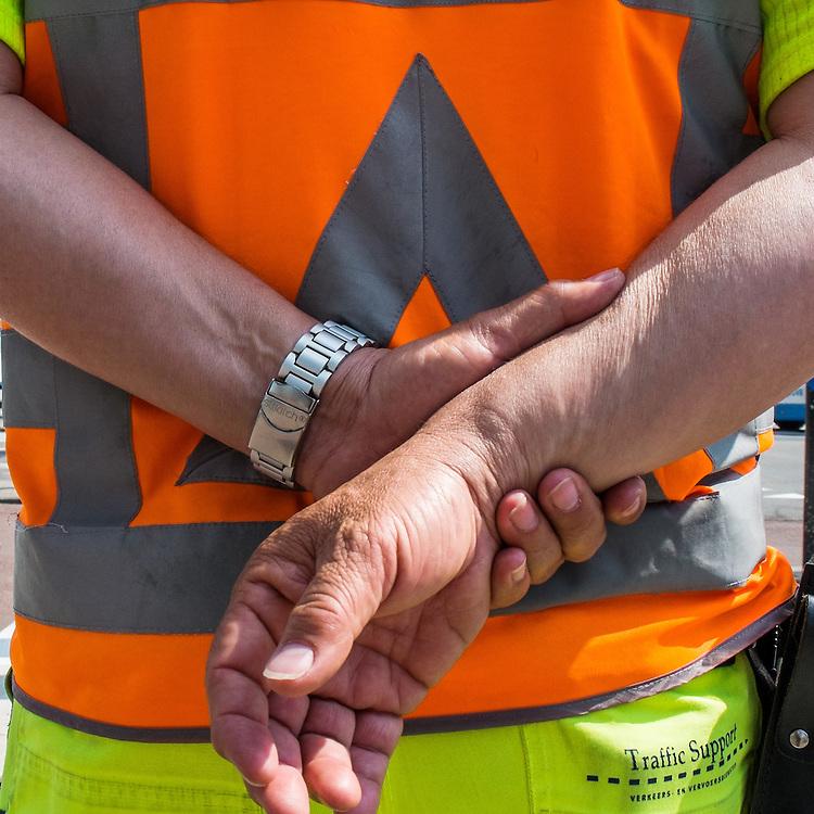 Nederland, Amsterdam, 7 mei 2013<br /> Traffic controller, verkeers regelaar houdt een kruispunt in de gaten met zijn handen op de rug.<br /> <br /> Foto(c): Michiel Wijnbergh