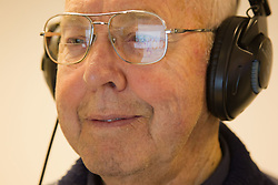 Computer class for people with visual impairments - man using headphones for audio, Google reflected in his glasses.