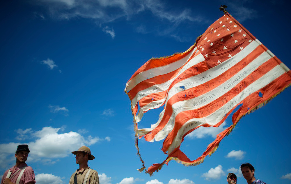 A 40 year old tattered flag from the 100th Ohio volunteers Union reenactors unit waves in the wind on the second of a four day Gettysburg Anniversary Committee 150th Gettysburg reenactment in Gettysburg, PA on July 5, 2013.