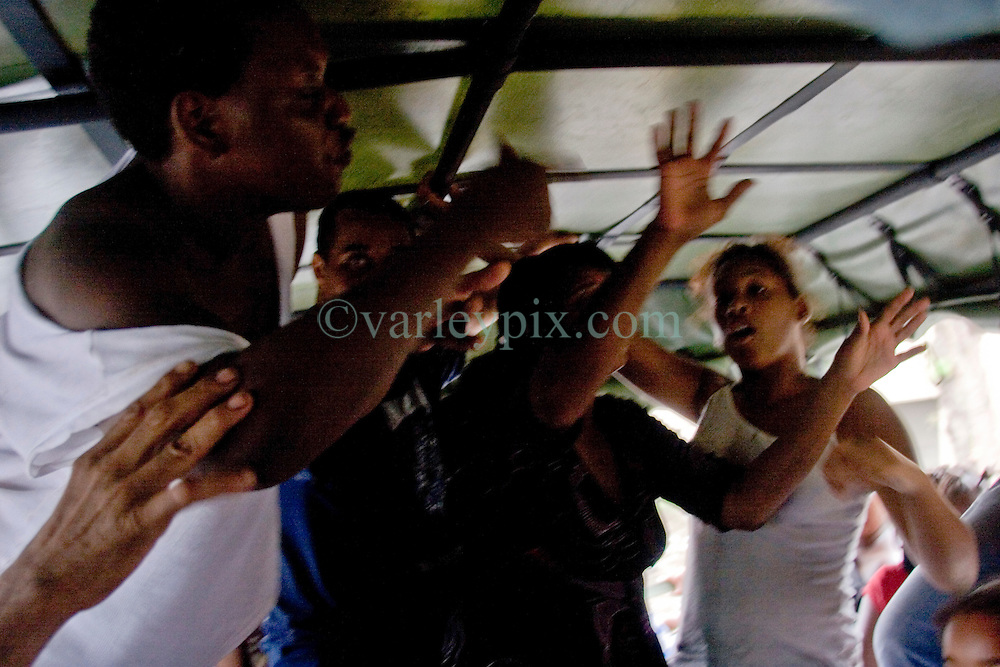 30 August, 2005. New Orleans Louisiana. Hurricane Katrina aftermath. <br /> A drunk woman (left) starts a fight on an army refugee truck taking people from the devastated lower 9th ward to the Superdome in New Orleans. Hundreds of desperate evacuees from the lower 9th ward await transportation to the Superdome where approximately 20,000 storm evacuees are housed.<br /> Photo Credit: Charlie Varley/varleypix.com