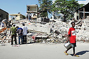 Neighbors come together in downtown Port-au-Prince -- just blocks from the Presidential Palace -- to sift through the rubble and salvage usable building materials and personal objects.