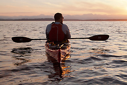 North America, United States, Washington, man at rest in kayak at sunset.  MR