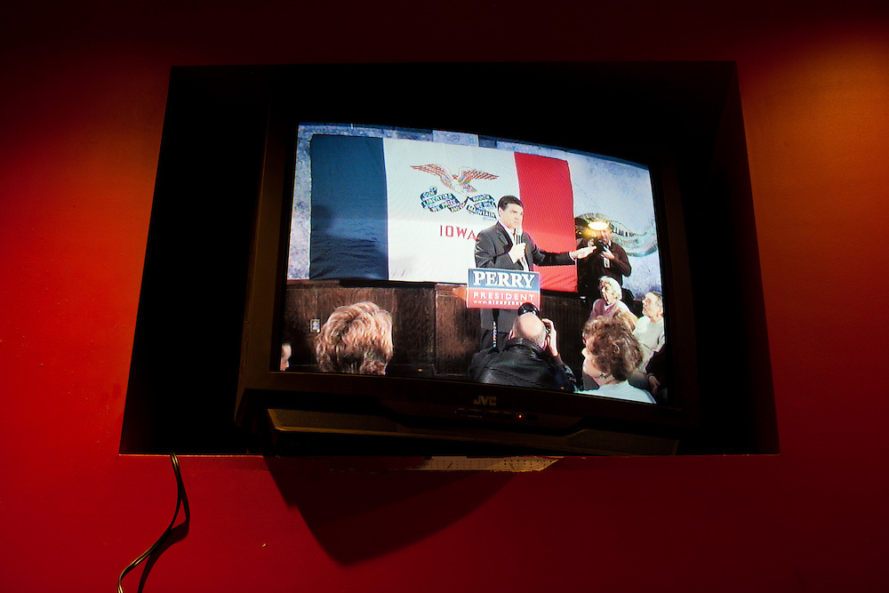 Republican presidential candidate Rick Perry is seen on a television monitor in an overflow area as he speaks at a campaign event at Doughy Joey's Pizza on Friday, December 30, 2011 in Waterloo, IA.
