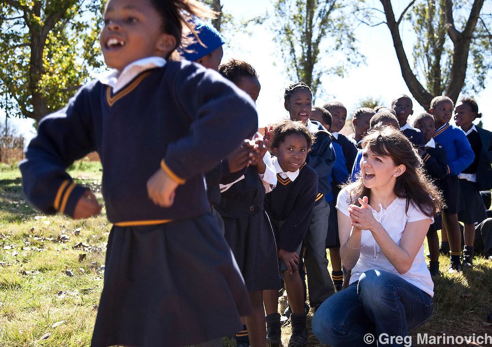 Alice Gilkes from Starfish meets and interacts with children at Sedibutho primary school in Chiawelo, Soweto, South Africa. 250 of the children at this school are assisted by Ms Tony Gloria Bodibe (in orange) organisation called Tsogang Sechaba. After school these children and many from other schools come to eat at the centre, or take home a lunchbox of food. All the children are vulnerable or orphans. Photo Greg Marinovich