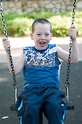 Young boy of 5 on a swing in a playground