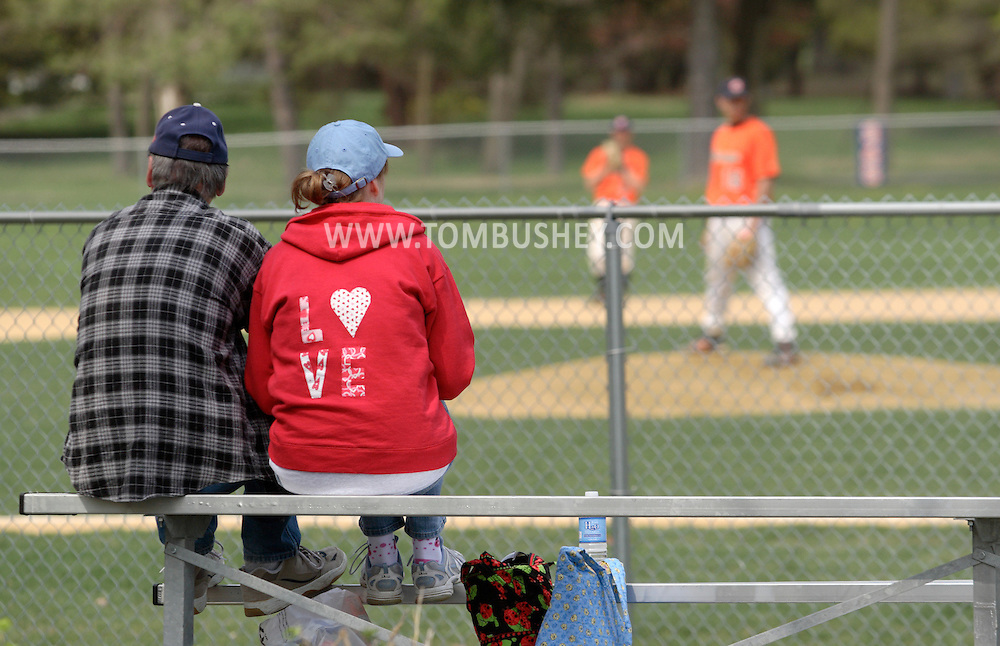 Middletown, NY - A man and a woman sit on the bleacher and watch SUNY Orange play a Region XV baseball game against Dutchess Community College on April 26, 2008.