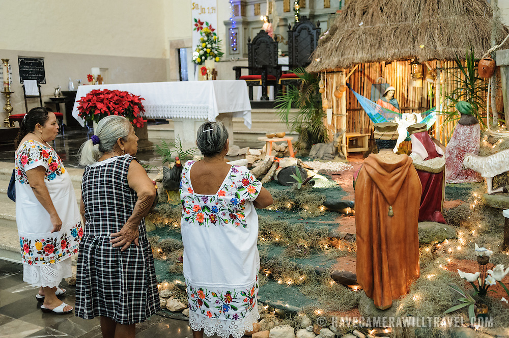 Three woman admire the Christmas nativity scene in the Spanish colonial Cathedral of San Gervasio (Catedral De San Gervasio) in Valladolid in the heart of Mexico's Yucatan Peninsula.