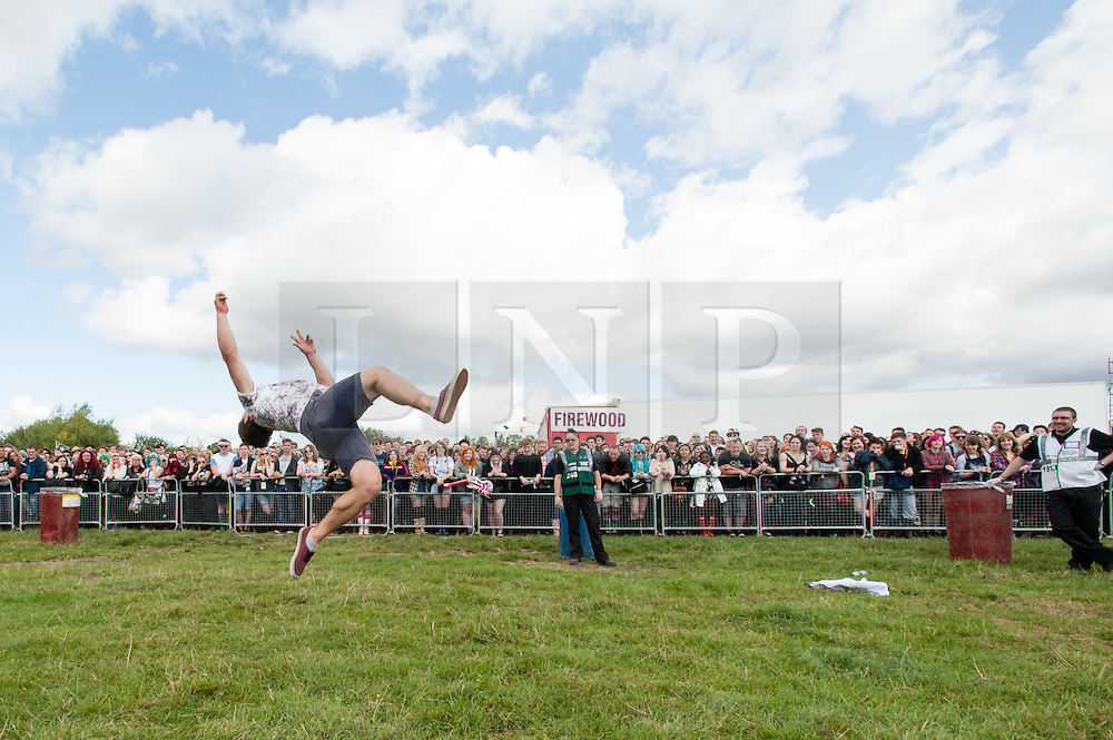 © Licensed to London News Pictures. 22/08/2014. Reading, UK.   Festival goers at Reading Festival 2014 on Friday morning, the opening day.  Here a festival goer competes with a festival organiser in an acrobatic competition as they wait for the gates to the main festival arena open.   The weather is sunny with light cloud.   Today is expected to remain dry with a 25% risk of showers.  Photo credit : Richard Isaac/LNP