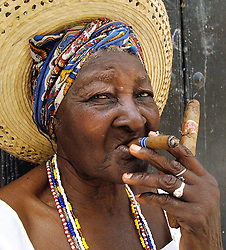 A Habanera smoking a cigar on a street in Havana, Cuba, on August 6, 2006, six days after an ailing Fidel Castro handed his brother Raul provisional control over the government which he has led uninterrupted for 47 years. Cuban citizens are waiting to find out if the 'Lider Maximo' will resume leadership after his recovery from an intestinal surgery. Photo by ABACAPRESS.COM | 103042_33