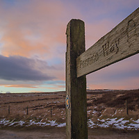 A sign indicating the Pennine Way at sunset on Brun Moor on the Marsden Moor Estate, Saddleworth, West Yorkshire.