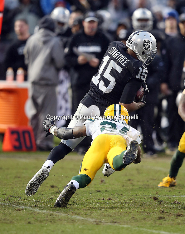 Green Bay Packers cornerback Quinten Rollins (24) dives while trying to tackle Oakland Raiders wide receiver Michael Crabtree (15) after a pass reception during the 2015 week 15 regular season NFL football game against the Oakland Raiders on Sunday, Dec. 20, 2015 in Oakland, Calif. The Packers won the game 30-20. (©Paul Anthony Spinelli)