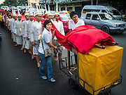18 NOVEMBER 2015 - BANGKOK, THAILAND:  Men in traditional Brahmin priests outfits  spool out a red cloth with prayers written on it at the start of the Wat Saket annual temple annual fair. Wat Saket is on a man-made hill in the historic section of Bangkok. The temple has golden spire that is 260 feet high which was the highest point in Bangkok for more than 100 years. The temple construction began in the 1800s in the reign of King Rama III and was completed in the reign of King Rama IV. The annual temple fair is held on the 12th lunar month, for nine days around the November full moon. During the fair a red cloth (reminiscent of a monk's robe) is placed around the Golden Mount while the temple grounds hosts Thai traditional theatre, food stalls and traditional shows.     PHOTO BY JACK KURTZ