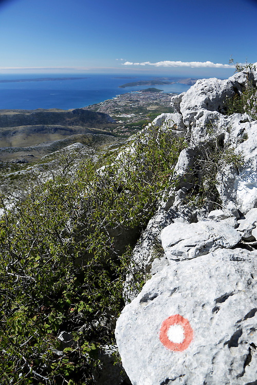 Trail marking on the Mosor mountain and the view to the ancient Dalmatian city of Split, Croatia.