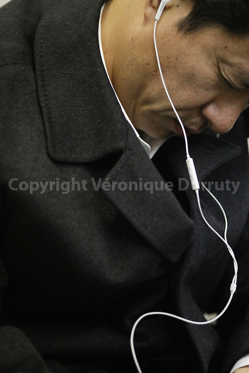 Man asleep, listening to music,Tokyo metro, Japan / Homme endormi, ecoutant de la musique au casque dans le metro de Tokyo, Japon