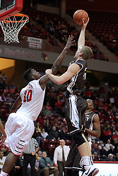 29 December 2014:  Evan McGaughey extends the ball over John Jones during an NCAA non-conference interdivisional exhibition game between the Quincy University Hawks and the Illinois State University Redbirds at Redbird Arena in Normal Illinois.