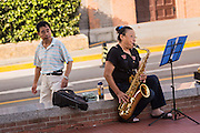 A man watches a women play the saxophone on the streets of Shanghai, China