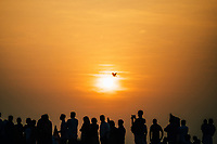 Fort Kochi, India -- February 11, 2018: Crowds watch the sunset over the water at Mahatma Gandhi Beach.