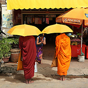 Kampot, Cambodia:  In the colonial city of Kampot, Buddhist monks receive food and money donations in exchange for prayers from the faithful.<br />