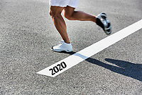 Man running on white line with year 2020 sign
