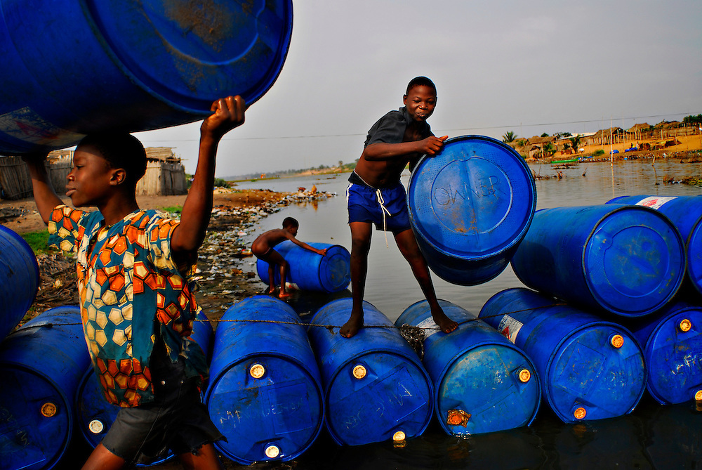 """12-01-29  --  ANEHO, TOGO  --   Boys carry empty 240 litre barrels to a warehouse near the Togo-Benin border where tens of thousands of litres of illegal fuel are stored.  A smuggler, who declined giving his name, said the illegal fuel trade provides valuable jobs in a country where a large percentage of the population makes less than $1 USD per day. """"This continent is suffering too much. Fuel smuggling gives a job to a mother and allows her to send her son to school."""" Photo by Daniel Hayduk"""