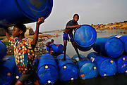 "12-01-29  --  ANEHO, TOGO  --   Boys carry empty 240 litre barrels to a warehouse near the Togo-Benin border where tens of thousands of litres of illegal fuel are stored.  A smuggler, who declined giving his name, said the illegal fuel trade provides valuable jobs in a country where a large percentage of the population makes less than $1 USD per day. ""This continent is suffering too much. Fuel smuggling gives a job to a mother and allows her to send her son to school."" Photo by Daniel Hayduk"