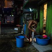 A migrant worker washing his cloths at back door of a restaurant at Jalan Tun Tan Siew Sin in Kuala Lumpur on November 19, 2017.