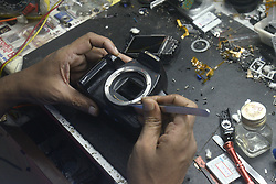 August 19, 2017 - Kolkata, West Bengal, India - Indian technician repairs digital cameras in a workshop in the occasion of World Photography day on August 19, 2017, in Kolkata.  World Photography Day celebrated by photographer and photo enthusiasts across the world annually on August 19, which is the day French Government patented the daguerreotype printing process and released it to the world for free in 1839. (Credit Image: © Saikat Paul/Pacific Press via ZUMA Wire)
