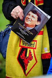 © Licensed to London News Pictures. 01/02/2017. Watford, UK. An order of service helfd next to a club scarf by a fan gathering for The funeral of former England football team manager Graham Taylor at St Mary's Church in Watford, Hertfordshire. The former England, Watford and Aston Villa manager,  who later went on to be chairman of Watford Football Club, died at the age of 72 from a suspected heart attack. Photo credit: Ben Cawthra/LNP