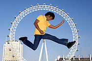 Young man playing air guitar in front of the Millennium Wheel in London. Photographed for Visit Britain as part of their Youth Culture campaign. THIS IMAGE IS COPYRIGHT VISIT BRITAIN.