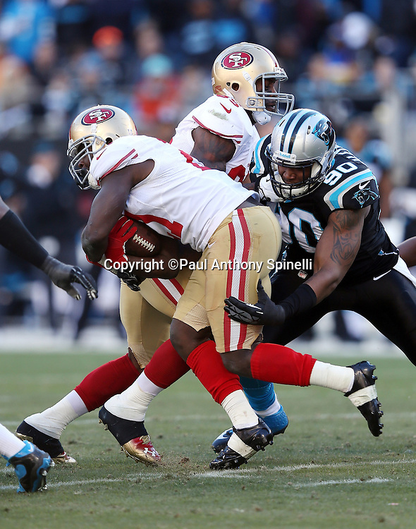 San Francisco 49ers running back Frank Gore (21) tries to avoid a tackle attempt by Carolina Panthers defensive end Frank Alexander (90) during the NFC Divisional Playoff NFL football game against the Carolina Panthers on Sunday, Jan. 12, 2014 in Charlotte, N.C. The 49ers won the game 23-10. ©Paul Anthony Spinelli