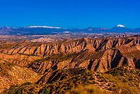 Badlands, seen from the Mirador Cueva los Amos viewpoint with snowcapped La Sagra peak in background, near Castillejar, Granada Province, Andalusia, Spain.
