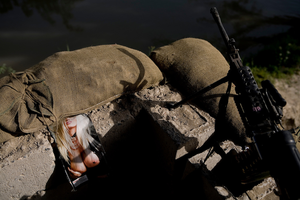 A pinup torn from a magazine keeps members of the 82nd Airborne company during a guard duty near Sangin, Helmand province, Afghanistan on Saturday, April 14, 2007.