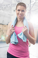 Portrait of happy woman with towel around neck standing in crossfit gym