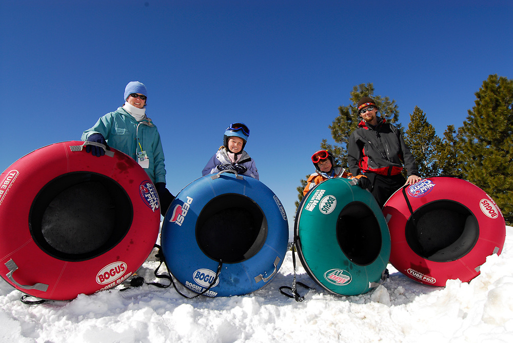 Idaho. Boise. Tubing Hill at Bogus Basin Resort.  Family of tubers holding colorful tubes ready to have some winter fun. MR