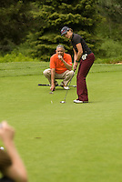 Group of adults checks the line for the putt on the golf green at Whistler Golf Course, Whistler, BC Canada.